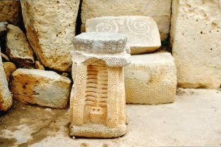 A low altar depicting in low relief a plant growing from a pot. In the background a spiral relief - From Hagar Qim.
